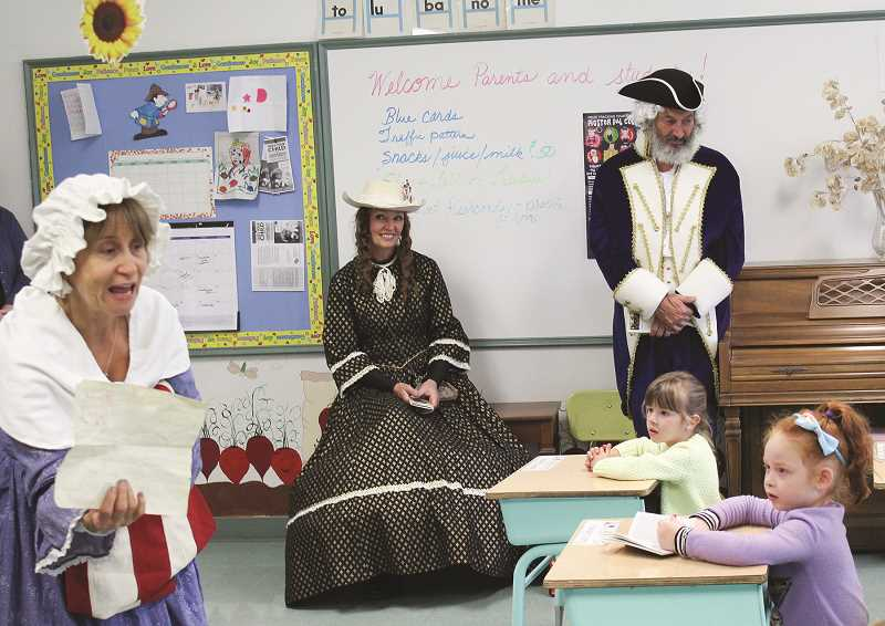 JASON CHANEY - Lorrie Peterson, left, portrays Betsy Ross during a presentation in Joanne Fenderson's kindergarten class at High Desert Christian Academy Wednesday to commemorate Constitution Week. Donna and Steve Hammond also dressed in colonial costumes.