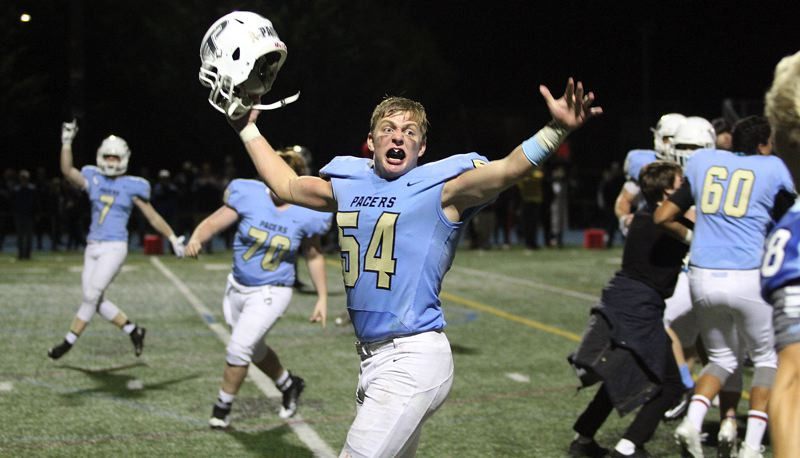 REVIEW PHOTO: MILES VANCE - Lakeridge senior linebacker Hunter Paulson and his teammates celebrate at the end of their 49-42 overtime win over Sherwood at Lakeridge High School on Friday night.