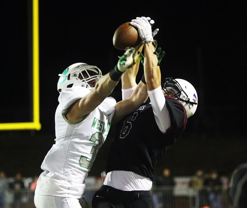 DAN BROOD - Tualatin senior receiver Jackson Willig (right) pulls in a pass as he's closely defended by West Linn senior Zack Huffstutter.