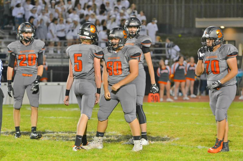 SPOTLIGHT PHOTO: JAKE MCNEAL - Scappoose senior defensive back Nicky Gill (20), senior linebacker Willy Lohman (5) and sophomore defensive linemen Jackson Lehman (60) and Robert Guajardo (70) celebrate late in the fourth quarter.