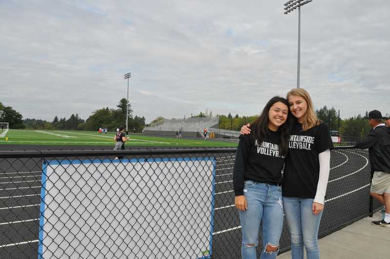 TIMES PHOTO: BLAIR STENVICK - Maddie Stoehr and Abby Jones, both members of Mountainside's women's volleyball team, cheered on 5K runners at Mountainside's grand opening celebration Saturday morning.