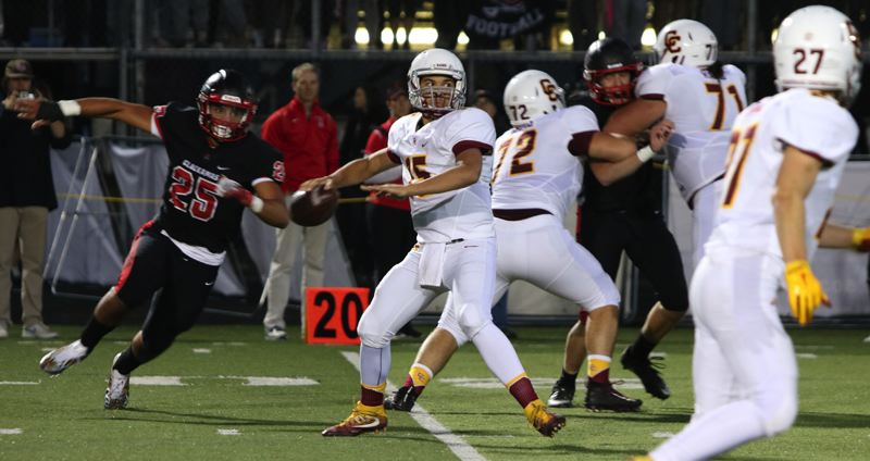 PAMPLIN MEDIA GROUP PHOTO: JIM BESEDA - Central Catholic quarterback Cade Knighton gets ready to throw a pass while Clackamas' Justice Pagan closes in during the Cavaliers' big win on Friday night.