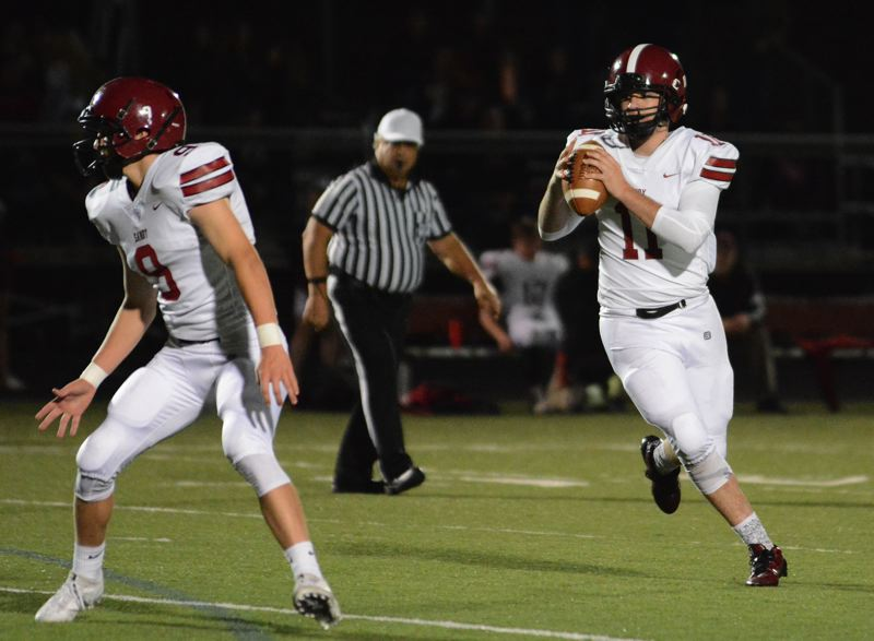 POST PHOTO: DAVID BALL - Sandy QB Tyler King rolls out and searches for a receiver during the second quarter of Friday's 26-12 win at Milwaukie.