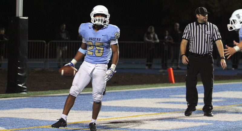 REVIEW PHOTO: MILES VANCE - Lakeridge running back Jalen John pops up after his two-yard touchdon run in overtime beat Sherwood 49-42 at Lakeridge High School on Friday.