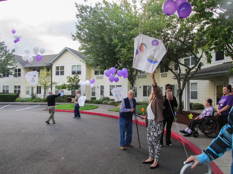 OUTLOOK PHOTO: TERESA CARSON - Residents and staff at Assisted Living at Summerplace 'fly' kites created by memory care residents to mark World Alzherimer's Day on Thursday, Sept. 21.