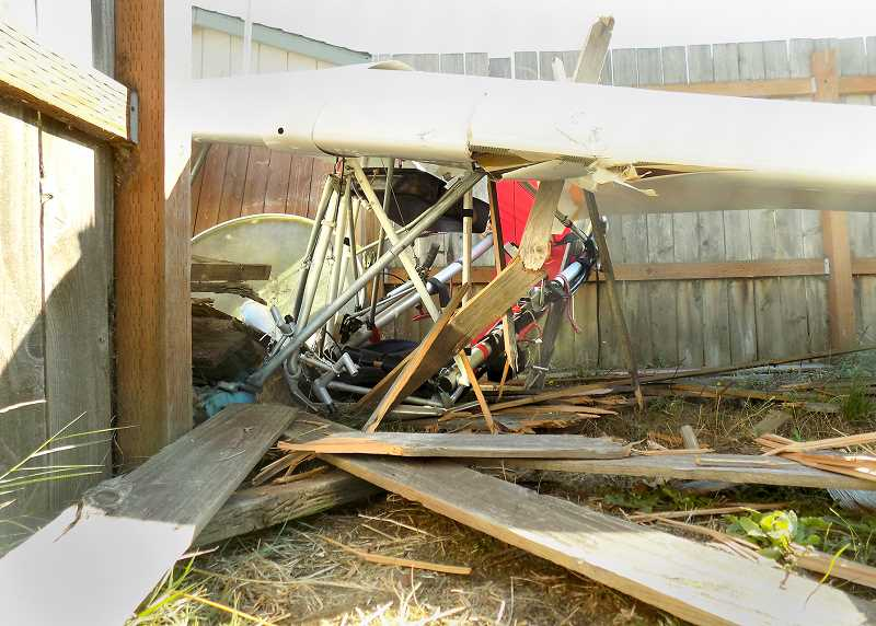 NDPD PHOTO - The remains of a power glider that crashed into the fence of a manufactured home park on Sandoz Road attest to the force with which the aircraft plummeted to the ground.
