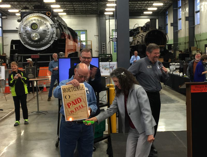 CITY OF PORTLAND - Commissioner Amanda Fritz burns the Oregon Rail Heritage Foundation's mortgage to the city as Commissioner Nick Fish applauds.