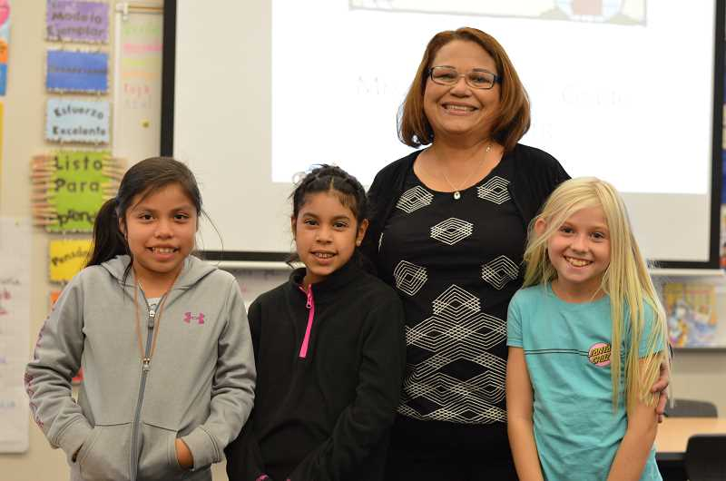 SPOKESMAN PHOTO: CLARA HOWELL  - Teacher Elisa Garcia poses with her third-grade students, Allison Zayago Enciso, 8, (left), Grace Garcia Esparza, 8, (middle) and Ellie Jeffries, 9, (right), at Lowries Curriculum Night.