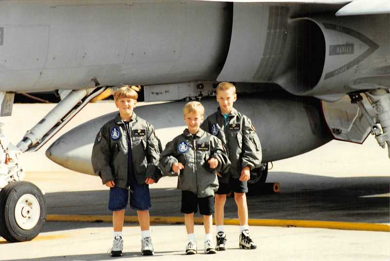 PHOTO COURTESY OF JNEANNE THEUS - Clad in U.S. Air Force jackets, Pat Gregoire's three sons stand in front of a fighter jet circa 1996, shortly after their father died.