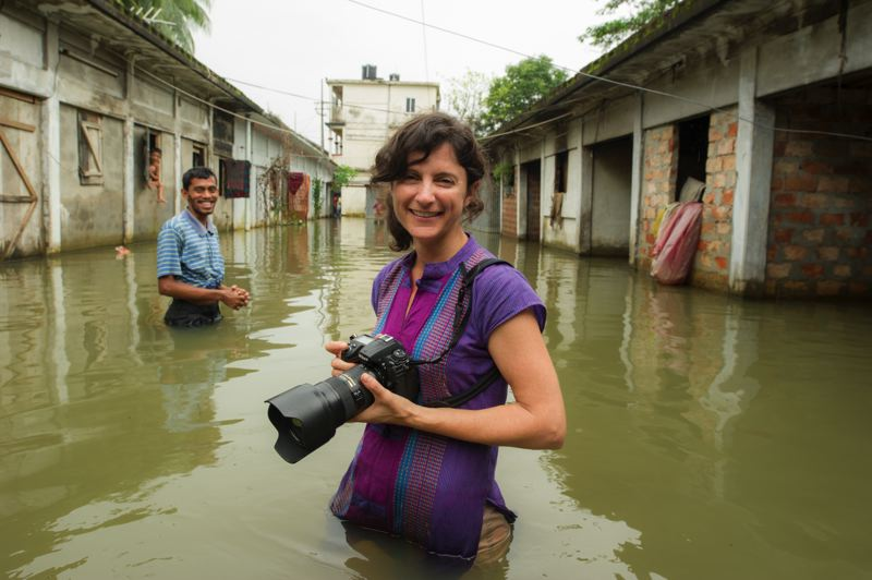 NATGEOLIVE/MICHAEL DAVIE - Ami Vitale photographing during a monsoon.