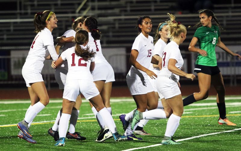 DAN BROOD - Members of the Sherwood High School girls soccer team celebrate after scoring a goal in the Lady Bowmen's Three Rivers League opener with Tigard. Sherwood got a 4-1 victory.