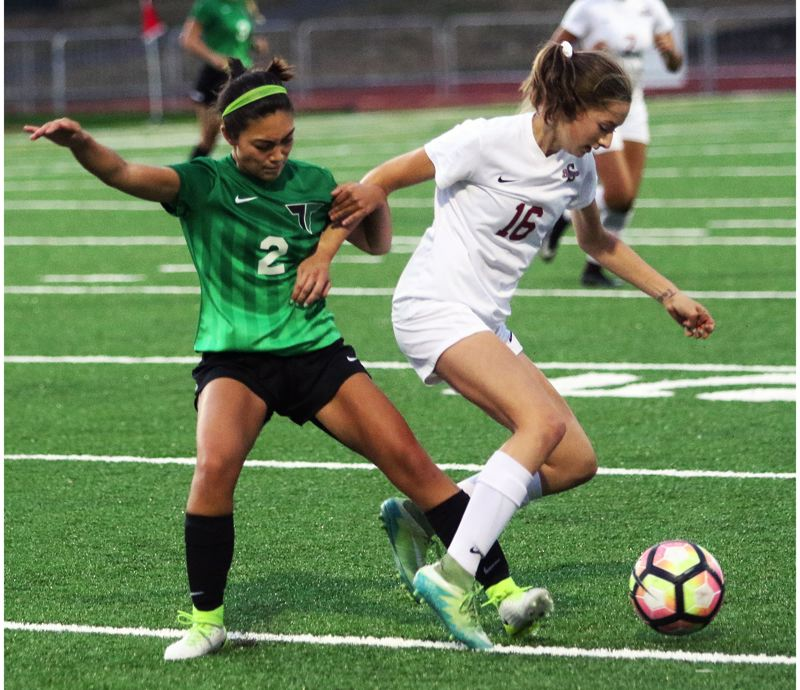 DAN BROOD - Tigard senior Kyra Medgin (left) and Sherwood sophomore Ava Boughey battle for the ball during last week's TRL-opening match.