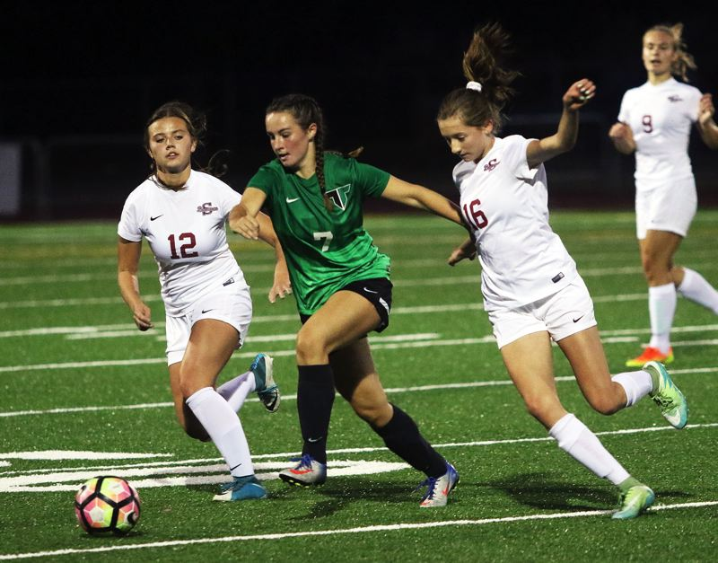 DAN BROOD - Tigard senior Alexandra Britch (7) looks to get to the ball between Sherwood junior Abby Eisenbeiss (12) and Ava Boughey.
