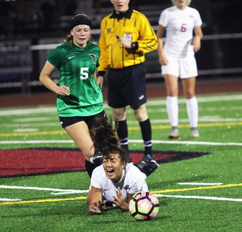 DAN BROOD - Sherwood sophomore Loma McNeese falls to the turf in front of Tigard junior Sydney Leinberger during the teams' league match.