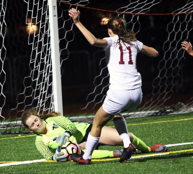 DAN BROOD - Tigard goalkeeper Natalie Carlson dives on the ball in front of Shewrood junior Mia Stallard during the teams' Three Rivers League match.