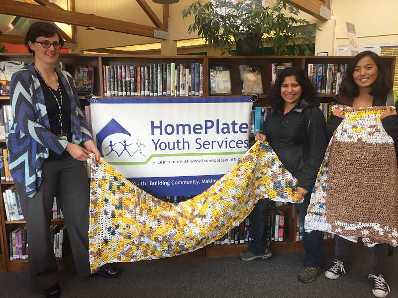 COURTESY PHOTO - Cornelius Public Library staff member Emily Antonelli (left) handed over two plastic mats to representatives from HomePlate Youth Services, who will give them to young people sleeping outside.