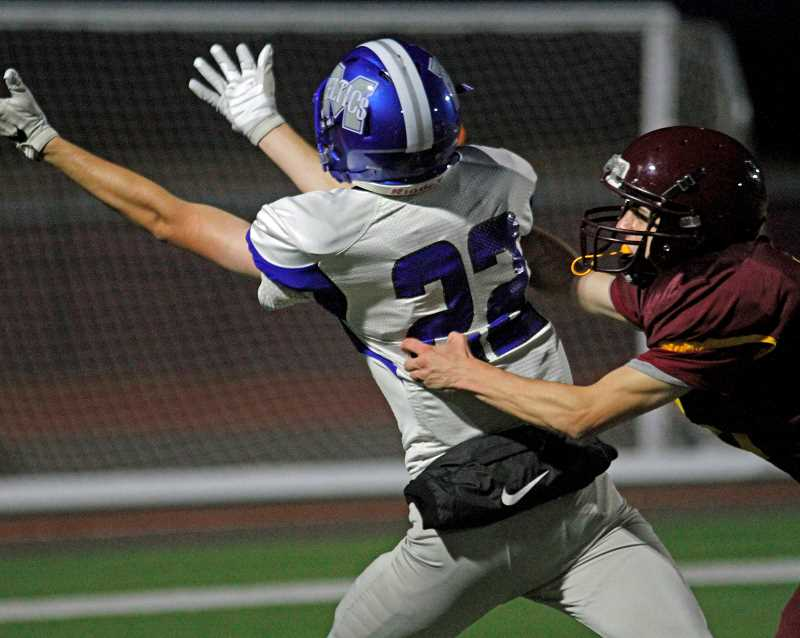 NEWS-TIMES PHOTO: WADE EVANSON - McNary's Kyle McCallister reaches for a pass with a Forest Grove defender grabbing on to him during their game September 29 at FGHS.