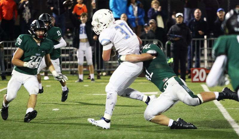 DAN BROOD - Lakeridge sophomore Matt Peterson looks to break away from Tigard defenders after catching a pass in Friday's game.