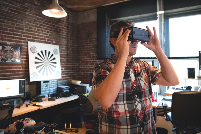PAMPLIN MEDIA GROUP: JAIME VALDEZ - Thomas Hayden, Co-Founder watches 360 degree video on a Samsung 8 phone in the office of 360 Labs.