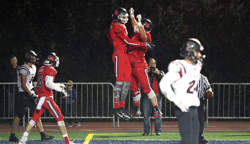 REVIEW PHOTO: MILES VANCE - Lake Oswego's Kameron Harvey (center) leaps into the air after scoring what turned out to be the winning touchdown in his team's 34-27 home win over Tualatin on Friday.