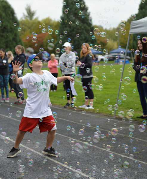 SPOKESMAN PHOTO: CLARA HOWELL - Third-grader Keenan Brimmer has fun with the bubbles right before the Fun Run begins.