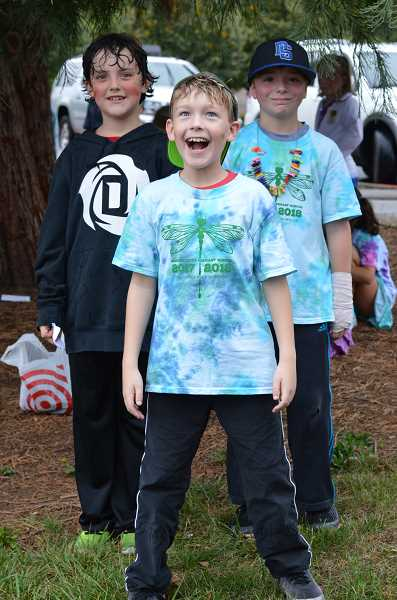 SPOKESMAN PHOTO: CLARA HOWELL - Lucas Moss, 9, (left), Wes Imholt, 9, (middle) and Alex Derlago, 10, (right) wind down after running laps on the Wood track for the Fun Run.
