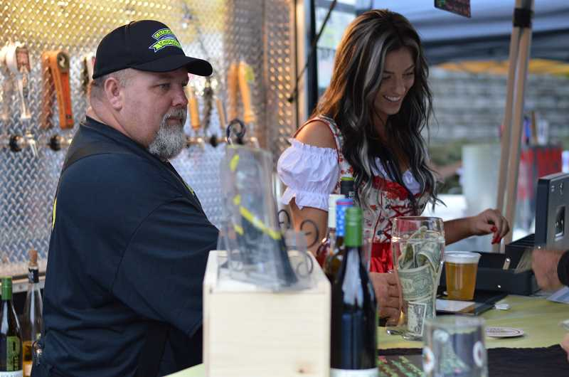 TIDINGS PHOTO: CLARA HOWELL - Tyke Murdock (left) and Tirzah Richman (right) serve several types of beer at West Linn's Oktoberfest.