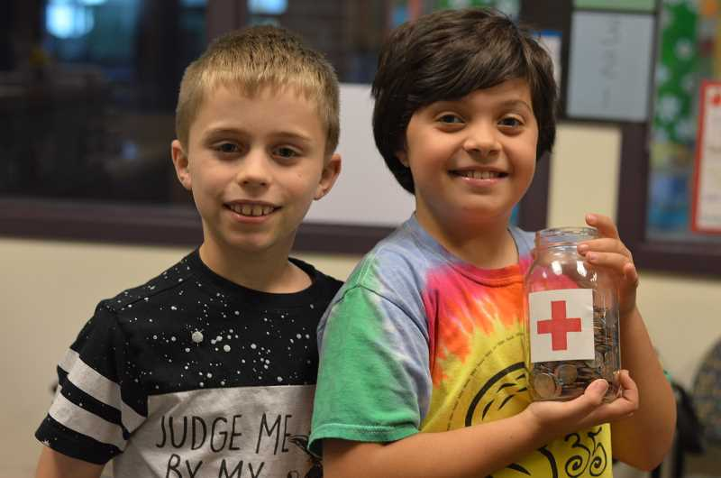 TIDINGS PHOTO: CLARA HOWELL - Willamette Primary Fourth-graders Macquarie Workman (left) and Jocelyn Caveney (right) show off the change jar from one of the classes before emptying it into the school change jar in the office.