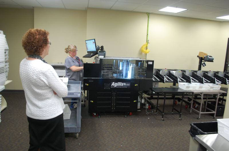 PHOTO BY: RAYMOND RENDLEMAN - Clackamas County Elections Clerk Sherry Hall watches ballot being accepted into a new machine that scans ballot signatures for inspection.