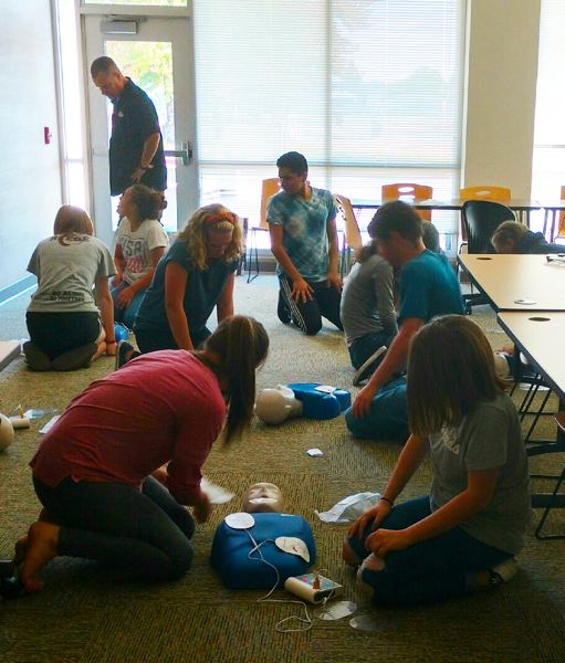 Kirk Stemple of the Gladstone Fire Department instructs Gladstone High School athletes on cardio-pulmonary resuscitation.