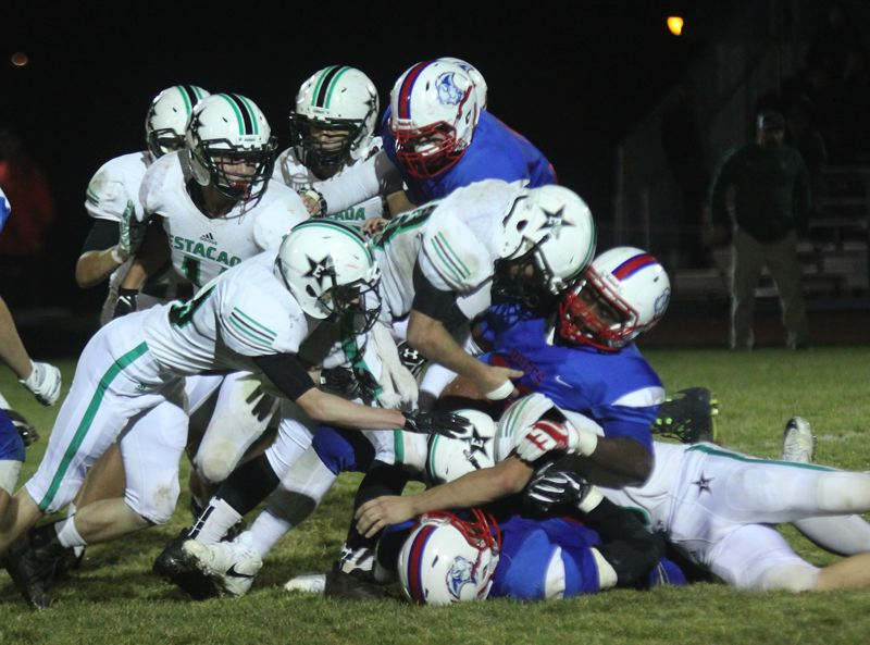 PAMPLIN MEDIA GROUP: WILL DENNER - A crowd of Estacada tacklers bring a Madras ball carrier to a stop during last Fridays 46-21 road win.