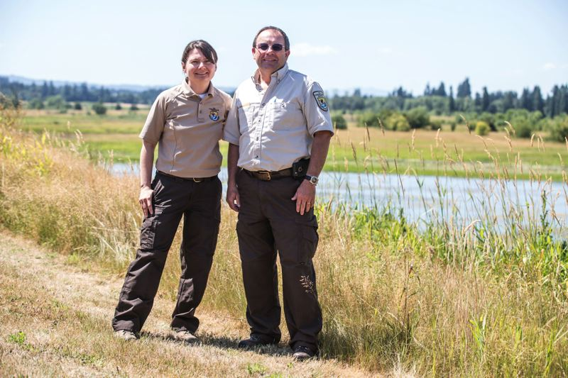 TIMES PHOTO: JONATHAN HOUSE - Eva Kristofik, left, and Larry Klimek, who work at the Tualatin River National Wildlife Refuge, stand in front of marshlands outside the refuge headquarters near Sherwood.