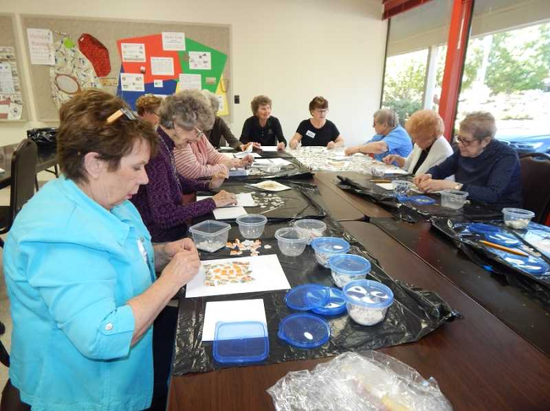 BARBARA SHERMAN - Members of the Summerfield Craft Club decorate trivets or photo frames with pieces of chipped china during a special meeting of the club led by member Lydia Cooper.