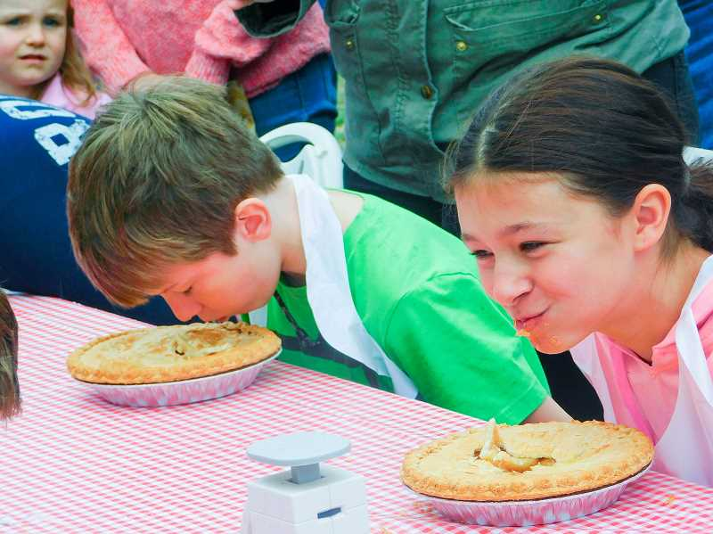 ESTACADA NEWS PHOTO: EMILY LINDSTRAND - Pie eating contest participants strive to consume as much pie as possible during the competition.
