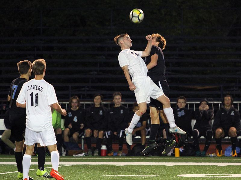 REVIEW PHOTO: MILES VANCE - Lake Oswego senior Chase Cumberland goes high into the air for a header during his team's 2-2 tie against Lakeridge at Lake Oswego High School on Monday.