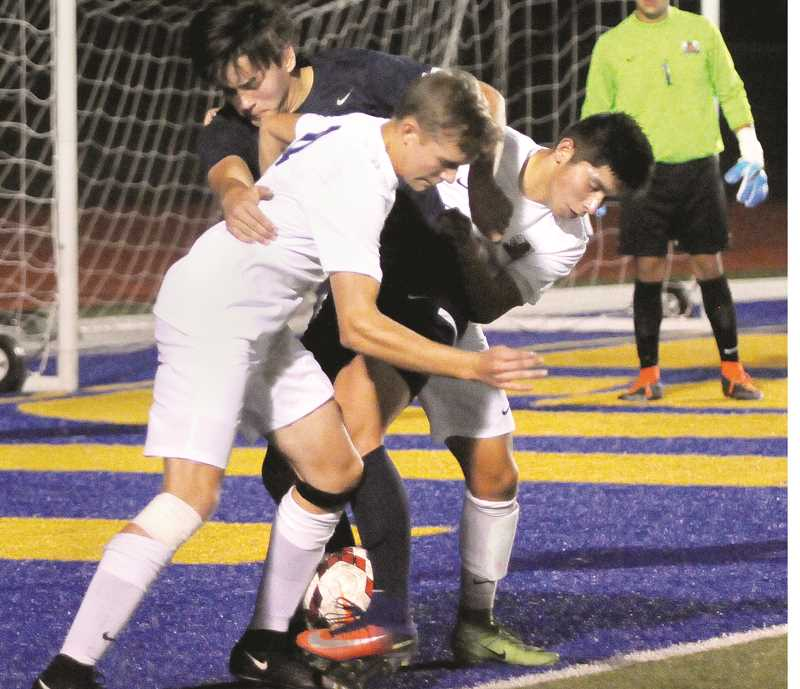 SETH GORDON - Newberg's Dawson Willems (left) and Alan Rodriguez get tied up with Lake Oswego's Ryan Seaman during the Tigers' 3-1 home victory Sept. 28. Rodriguez scored the winning goal early in the second half.