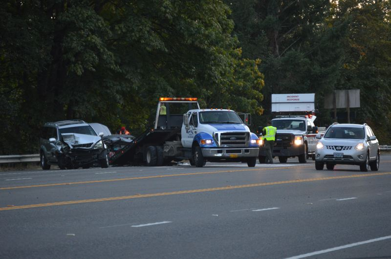 SPOTLIGHT PHOTO: COURTNEY VAUGHN - Mangled vehicles are loaded on a tow truck Tuesday evening, Oct. 3, after a major crash that heavily bakced up traffic in both directions of Highway 30 and sent at least one person to the hospital.