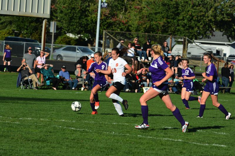 SPOTLIGHT PHOTO: JAKE MCNEAL - Indians freshman midfielder Grace Negelspach (18) contends with Astoria freshman midfielder Elle Espelien (9) for control of a pass.