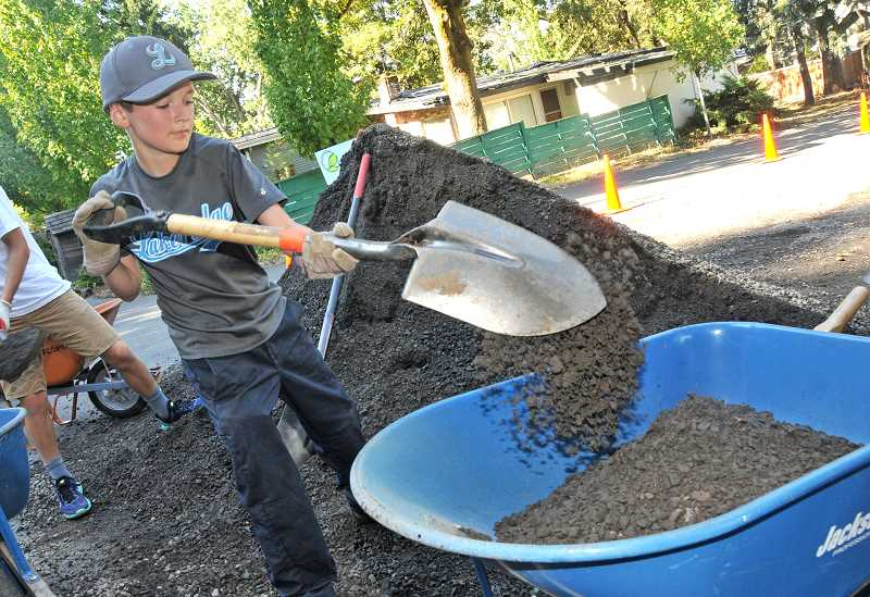 REVIEW PHOTO: VERN UYETAKE - Finn Rolstad fills a wheelbarrow with gravel during a recent Friends of Hallinan Heights Woods work party. Children are encouraged to take part in most of the City's stewardship efforts.