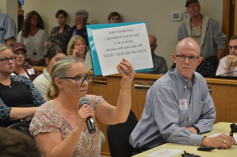 SPOTLIGHT PHOTO: NICOLE THILL - Leah Tillotson, a St. Helens resident who own the Columbia Theater, holds up a sign describing how a food combo offered at her place of business would be affected by a proposed sugar-sweetened beverage tax.