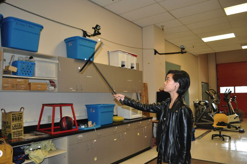 TIMES PHOTO: BLAIR STENVICK - Jane Hang uses a pole with markers on the end to help Beaverton Health and Science School's motion-sensing cameras identify the space.