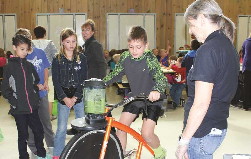 HOLLY SCHOLZ/CENTRAL OREGONIAN - CRE fourth-grader Alex Maghan takes a turn on the blender bike.