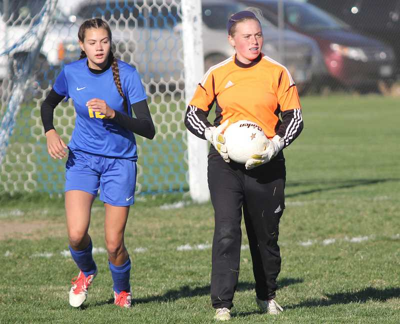 WILL DENNER/MADRAS PIONEER - Crook County goalkeeper Hazel Hoffman holds the ball after making a stop Tuesday against the Madras White Buffalos, while defender Emma Hehn starts to run up the field. Madras won the match 4-0.