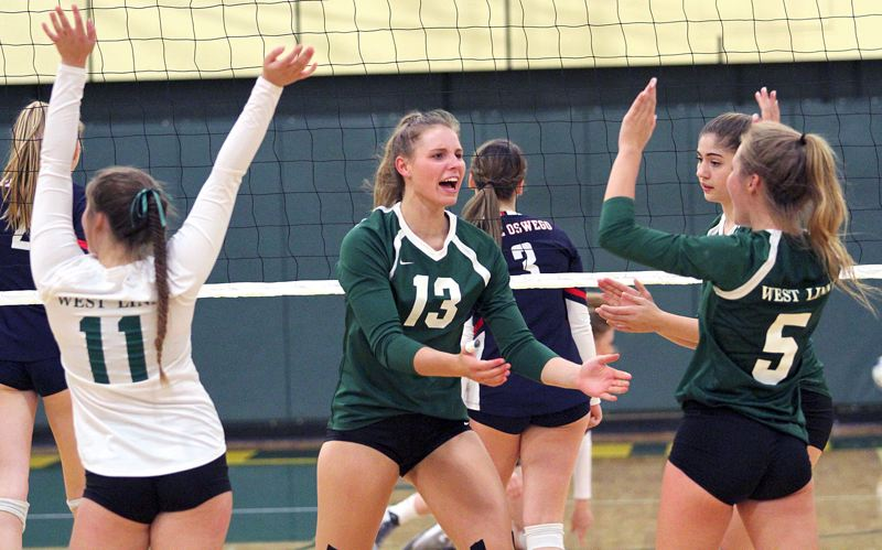 TIDINGS PHOTO: MILES VANCE - West Linn Makayla Long (center) accepts congratulations from Callista Noel during their team's three-set sweep of Lake Oswego at West Linn High School on Thursday.
