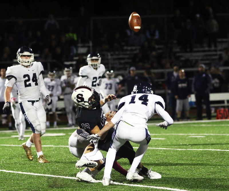 DAN BROOD - The ball is knocked up in the air as Sherwood senior quarterback Wyatt Zettlemoyer, who went out on a pass pattern this play, is hit by Lake Oswego sophomore Thomas Dukart, and other Lakers.