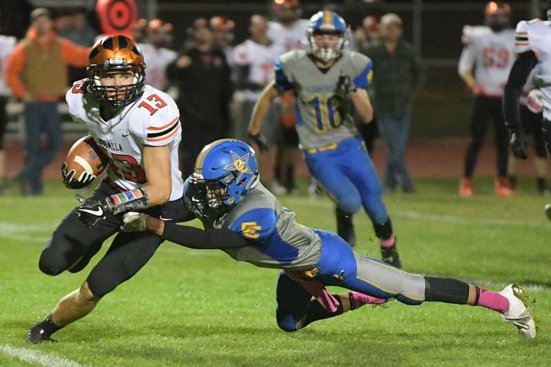 LON AUSTIN/CENTRAL OREGONIAN - Molalla's Jeff Larsen is tackled after catching a pass for a big gain. Larsen caught five passes for 197-yards in a losing cause as the Indians lost to the Crook County Cowboys 21-12.