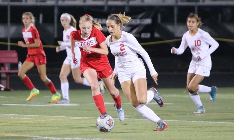 REVIEW/NEWS PHOTO: JIM BESEDA - Clackamas' Jaycee Iranshad (2) tries to outrun Oregon City's Chloe Leonetti during the second half of Thursday's Mt. Hood Conference girls soccer match at Clackamas High School.