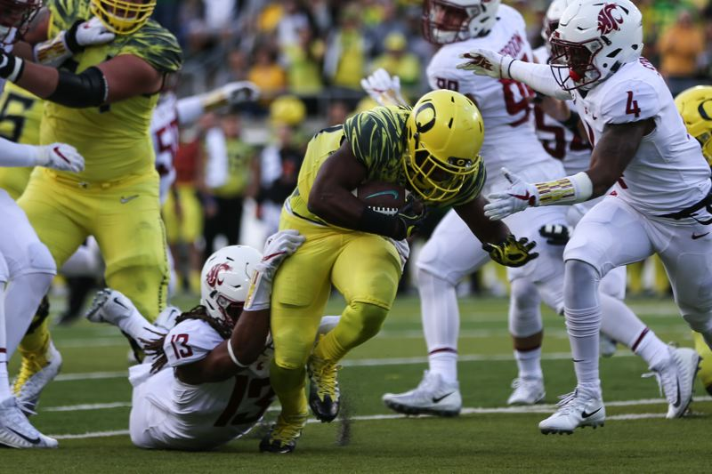 TRIBUNE PHOTO: DAVID BLAIR - Washington State closes in on Oregon running back Kani Benoit, with Jahad Woods making an ankle tackle.