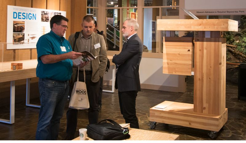 PHOTOS: PAUL BARNUM (COVER) AND INKA BAJANDAS  - (l-r) Timm Locke, director of forest products with the Oregon Forest Resources Institute, Doug Sheets, an associate with LEVER Architecture, and Tom Cody, managing principal with project^, discuss mass timber at the World Forestry Center exhibit called The Future of Tall: Mass Timber Innovation.
