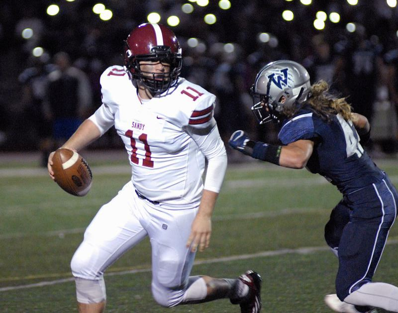POST PHOTO: MATT RAWLINGS - Sandy quarterback Tyler King tries to escape from a Wilsonville defender during his team's 48-14 loss at Wilsonville on Friday.